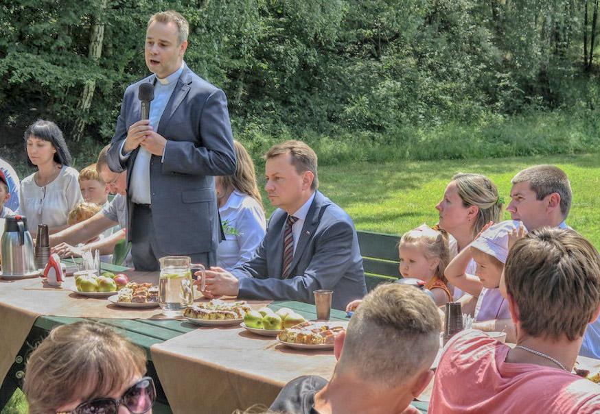 Minister Błaszczak i ks. Harkiewicz żegnają uchodźców. Źródło: ro.com.pl