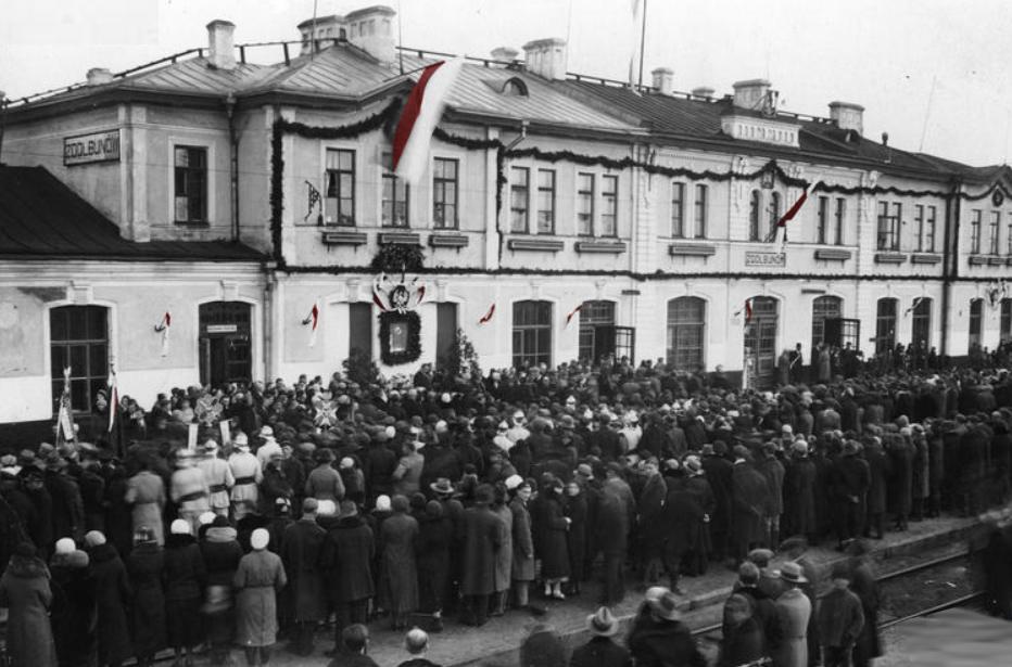 Tłum ludzi przed budynkiem stacji w Zdołbunowie w 1934 roku podczas uroczystości odsłonięcia tablicy pamiątkowej ku czci marszałka Józefa Piłsudskiego.