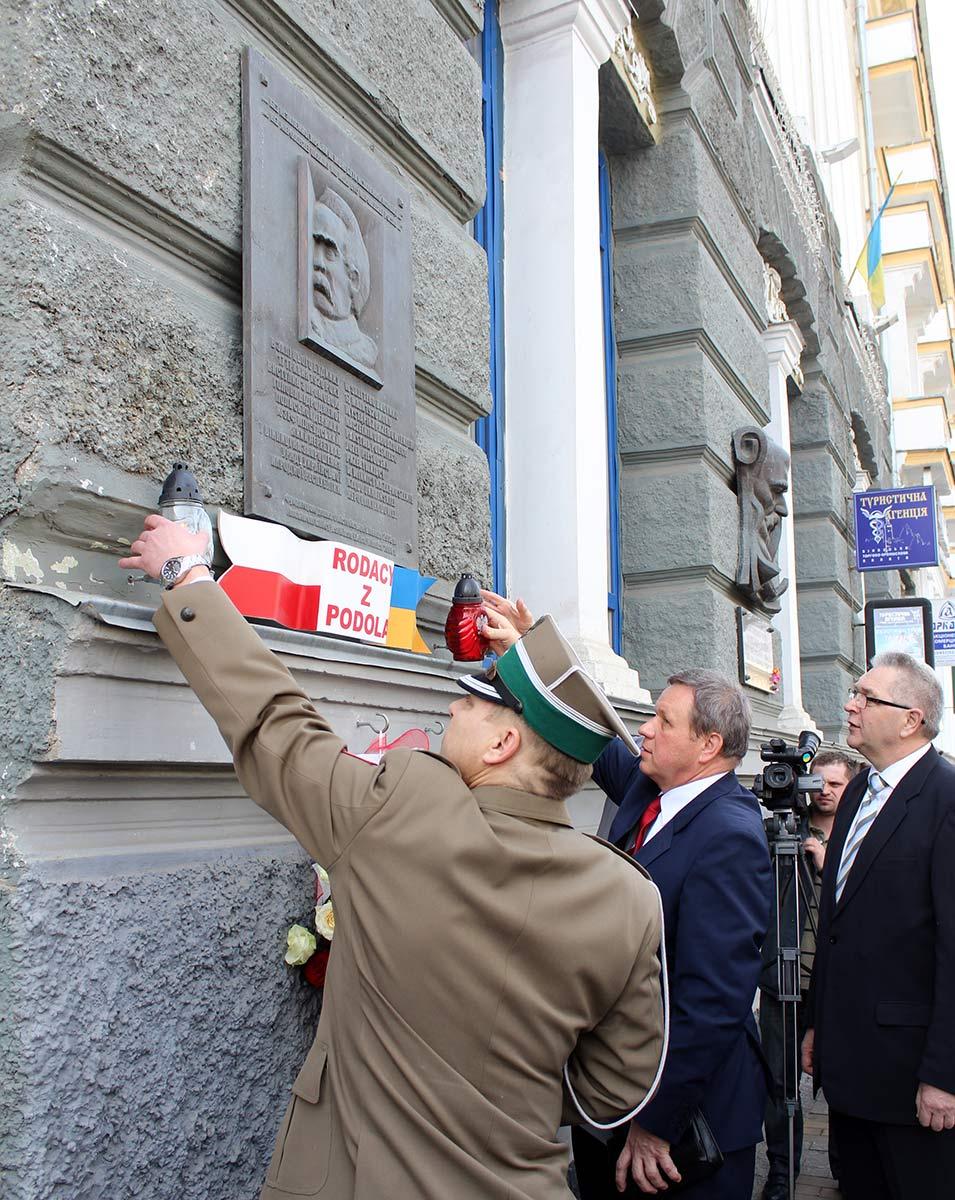 Ryszard Kobielak, Krzysztof Świderek i Krzysztof Rosiński składają kwiaty pod tablicą Marszałka
