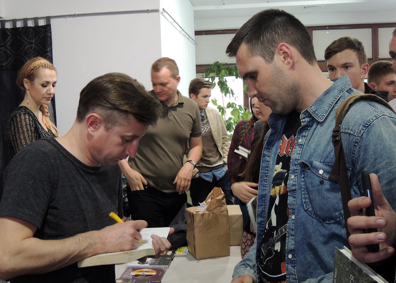 Serhij Żadan (po lewej) podpisuje własną książkę