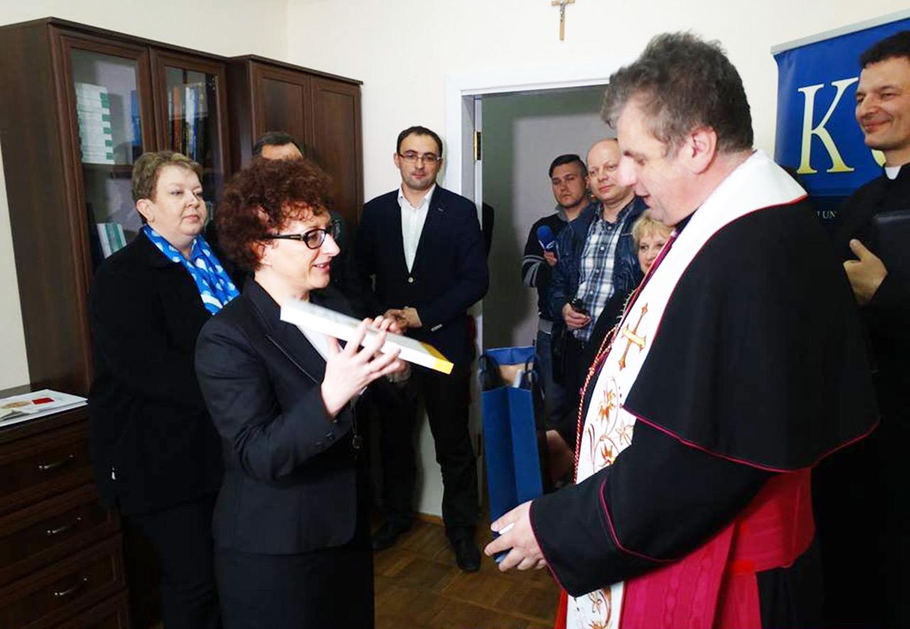 Prorektor KUL dr hab. Urszula Paprocka-Piotrowska prezentuje ks. Makowskiemu pamiętną lekturę