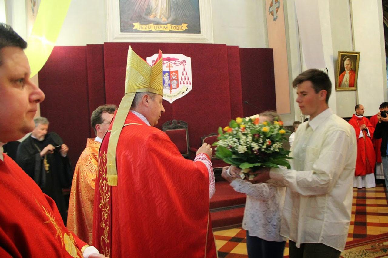 Biskup Piotr Malczuk przyjmuje w darze kawiaty od młodzieży