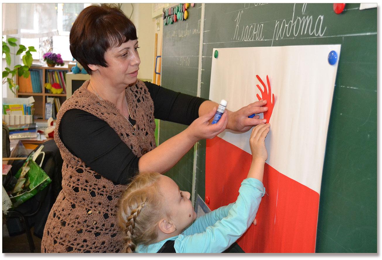 Na zdjęciu Pani Helena z Berdyczowa pomaga dzieciom tworzyć kompozycję patriotyczną