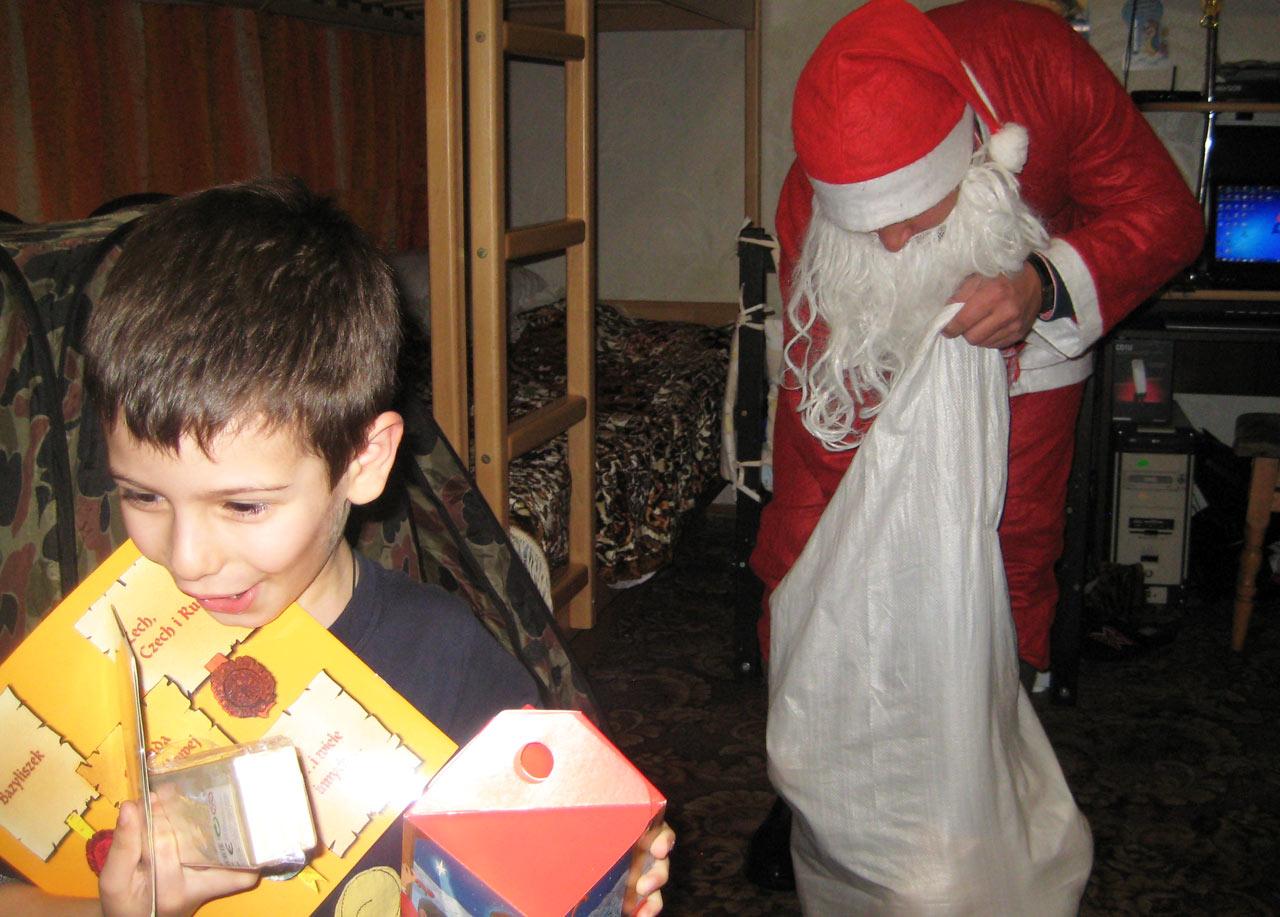 Na zdjęciu - mały Amir otrzymuje prezenty od Mikołaja